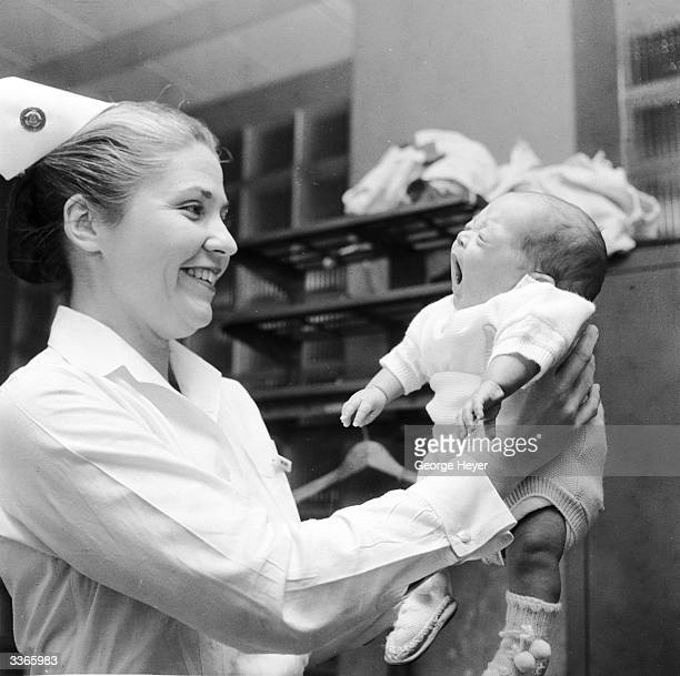Nurse Catherine Best Supervisor of the Premature Nursery lifting up a three month old baby boy at Mount Sinai Hospital in New York