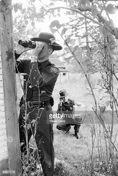 Officers of the US Border Patrol using binoculars to survey the area