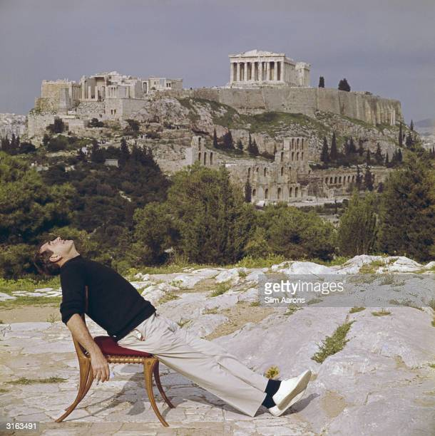Photographer Slim Aarons slouches in a chair with the Acropolis and its surroundings as a backdrop