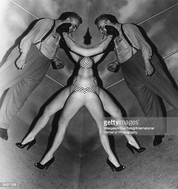Polishborn American photographer Arthur 'Weegee' Fellig with one of his female models Mirror effect/double image Photo by Weegee/International Center...
