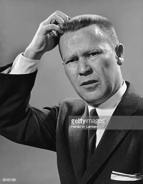 Portrait of a businessman with a crew cut scratching his head while looking confused 1950s