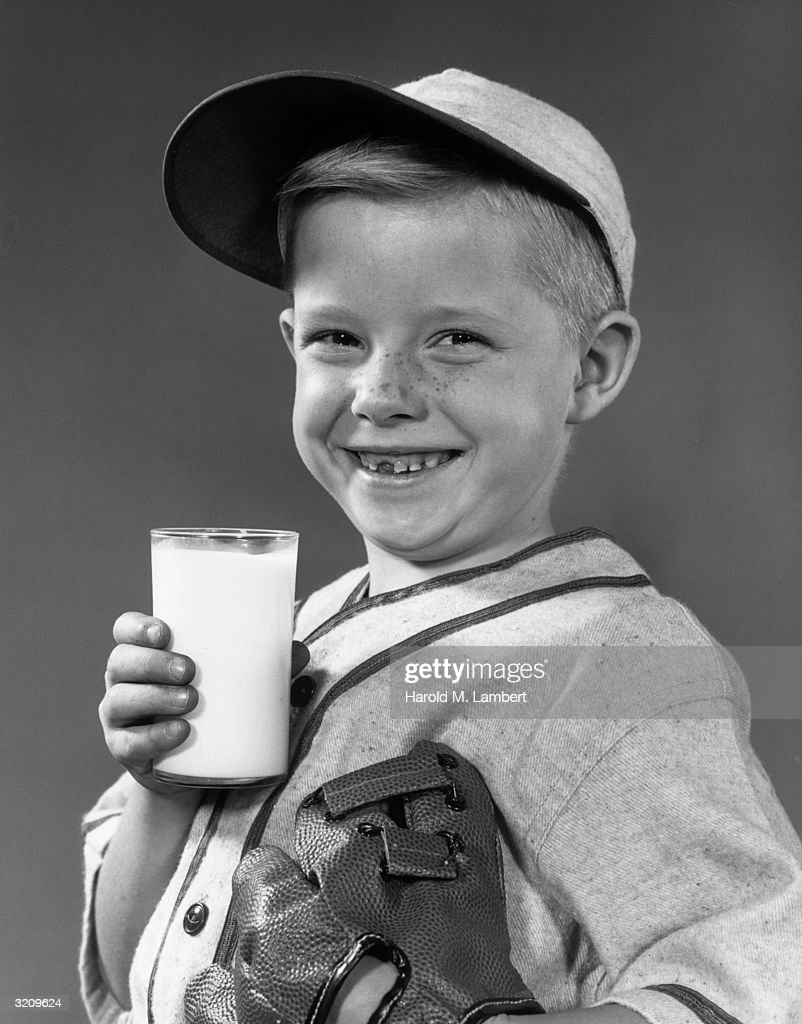 Portrait of a young boy smiling as he holds a glass of milk. He wears a baseball uniform and a glove on one hand. He is missing a front tooth.