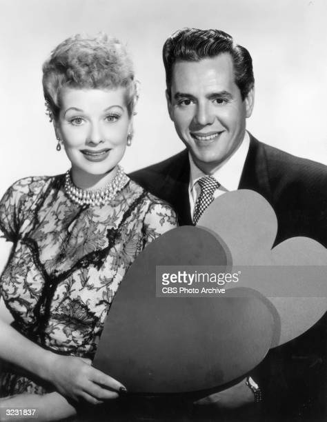 Portrait of American actor and comedian Lucille Ball and her husband, Cuban-born actor and bandleader Desi Arnaz , holding heart-shaped cutouts.