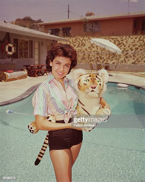 Portrait of American actor and Mickey Mouseketeer Annette Funicello smiling while standing by a pool and holding a stuffed tiger toy California...