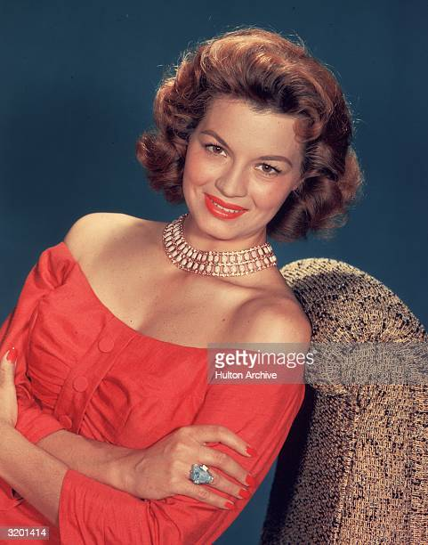 Portrait of American actor Angie Dickinson seated, wearing a coral, off-the-shoulder dress. She wears an ivory, jeweled necklace.