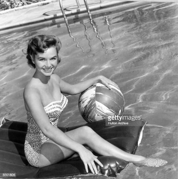Portrait of American actor Debbie Reynolds wearing a strapless onepiece swimsuit holding a beach ball while sitting on an air mattress in a swimming...