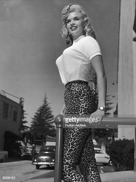 Portrait of American actor Jayne Mansfield standing outdoors in a light-colored T-shirt and leopard print pants.