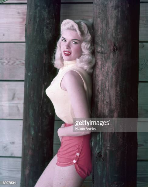 Portrait of American actor Jayne Mansfield, wearing a sleeveless sweater, pointy bra and red shorts, leaning against a wooden post, 1950s.