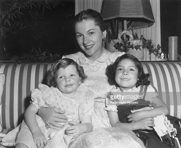 Portrait of American actor Joan Fontaine smiling and sitting with her daughter Deborah and her adopted Peruvian daughter on a striped sofa