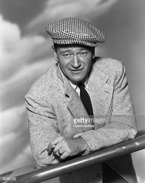 Portrait of American actor John Wayne leaning on a wooden bar holding a cigarette dressed in a suit and checkered cap