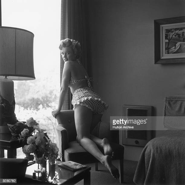 Portrait of American actor Marilyn Monroe wearing a polka dot twopiece swimsuit leaning on a chair next to a window in a living room mid1950s