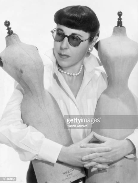 Portrait of American costume designer Edith Head embracing two miniature dressmaker dummies