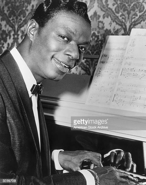 Portrait of American jazz singer and pianist Nat King Cole playing the piano