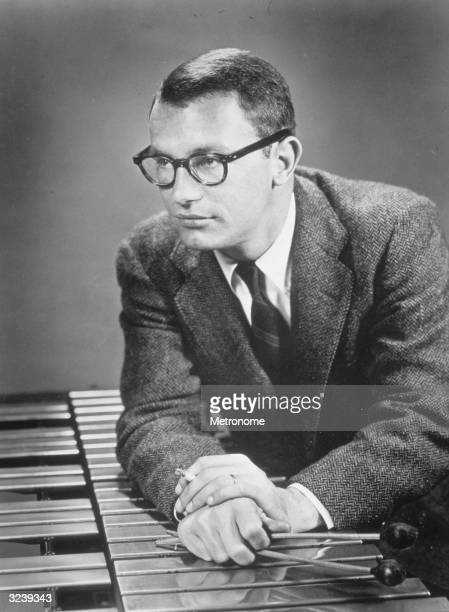 Portrait of American jazz vibraphonist Cal Tjader holding two mallets and leaning on a vibraphone while looking to the side