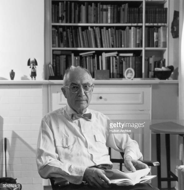 Portrait of American poet William Carlos Williams sitting in front of a bookcase with a book on his lap.