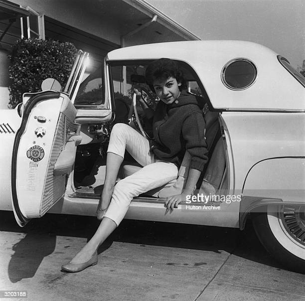 Portrait of American singer and actor Annette Funicello posing with her legs stretched out while preparing to exit a Ford Thunderbird