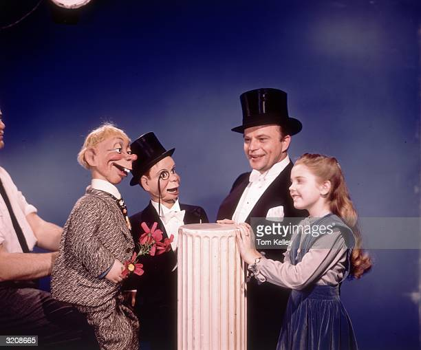 Portrait of American ventriloquist and comedian Edgar Bergen wearing a top hat and speaking next to his daughter Candice and two dummies Mortimer...