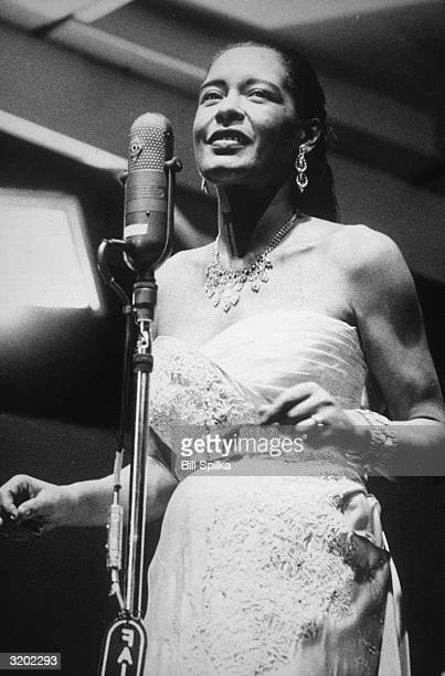 Portrait of Billie Holiday singing into a microphone wearing a strapless gown