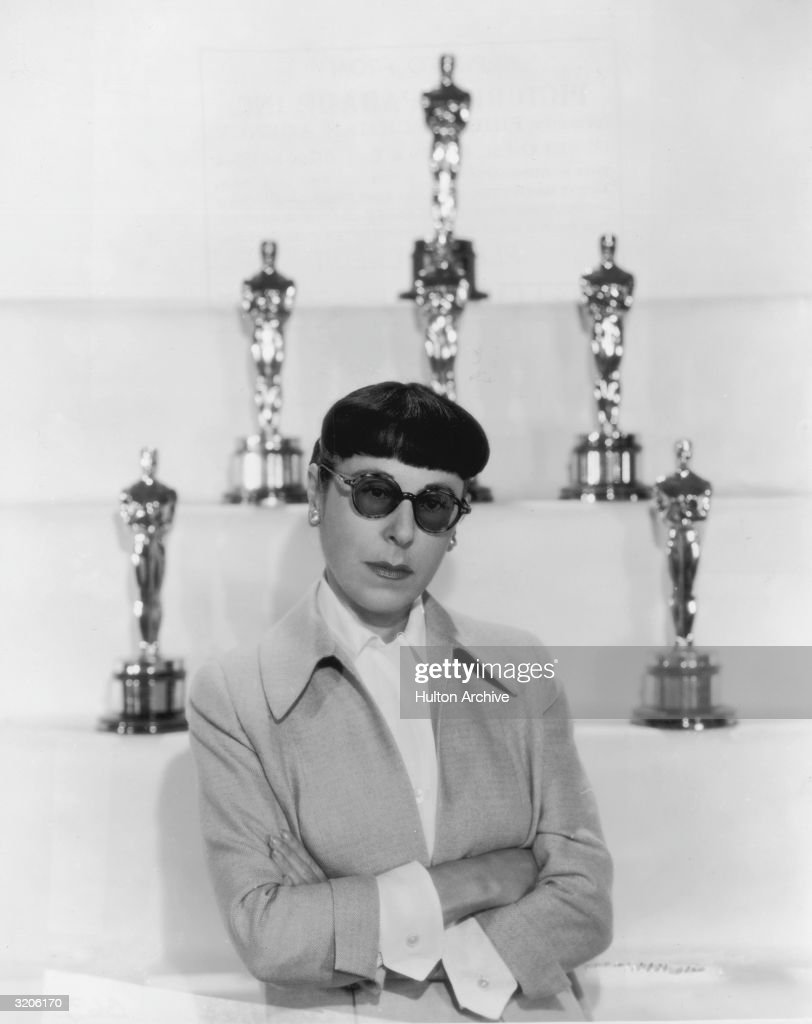 Portrait of Hollywood fashion designer Edith Head (1897 - 1981) posing with six of her Oscars for Costume Design. Head was Fashion Chief at Paramount Pictures. She wears her trademark dark, round-rimmed sunglasses.