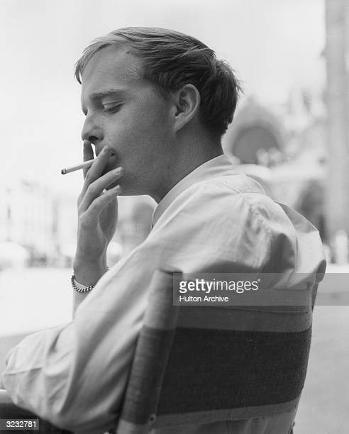 Profile view of American author Truman Capote smoking a cigarette at an outdoor cafe Venice Italy