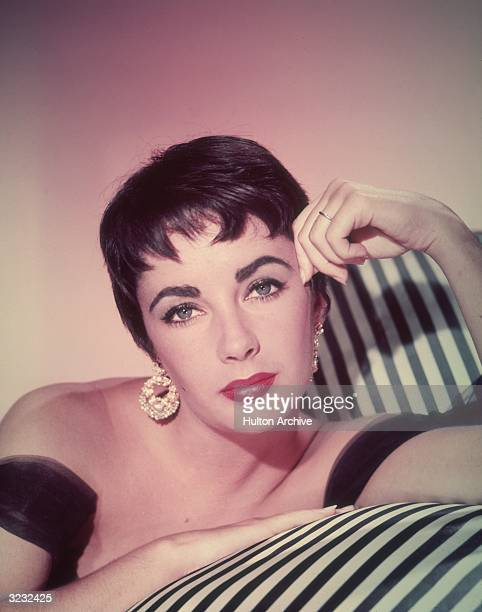Promotional headshot portrait of Britishborn actor Elizabeth Taylor leaning on a striped sofa in a sleeveless gown and short hair