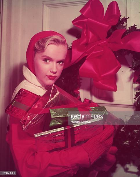 Promotional portrait of American actor Anne Francis holding an armful of wrapped Christmas presents standing outside a door with a large ribbon on it...