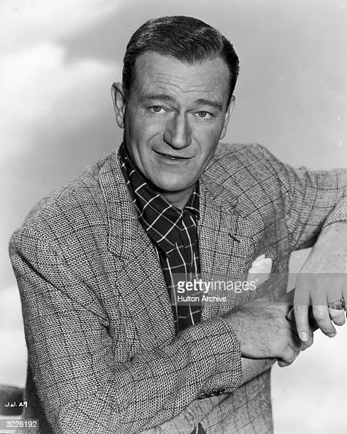 Promotional portrait of American actor John Wayne posing in a checkered sports jacket with his elbows resting on a wooden branch