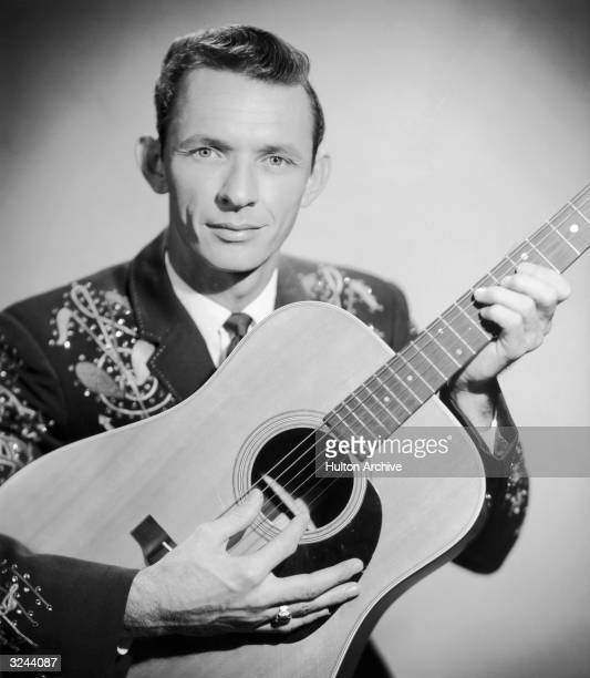 Promotional portrait of country music singer and songwriter Mel Tillis holding a guitar in an embroidered Western jacket