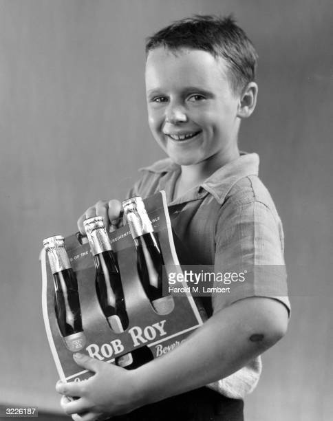 Promotional studio portrait of a boy holding a sixpack of Rob Roy bottled soda