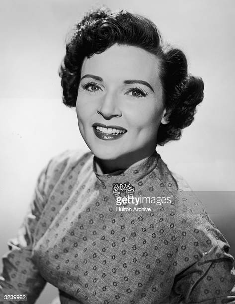 Promotional studio portrait of American actor Betty White smiling and wearing a patterned dress with a heartshaped brooch