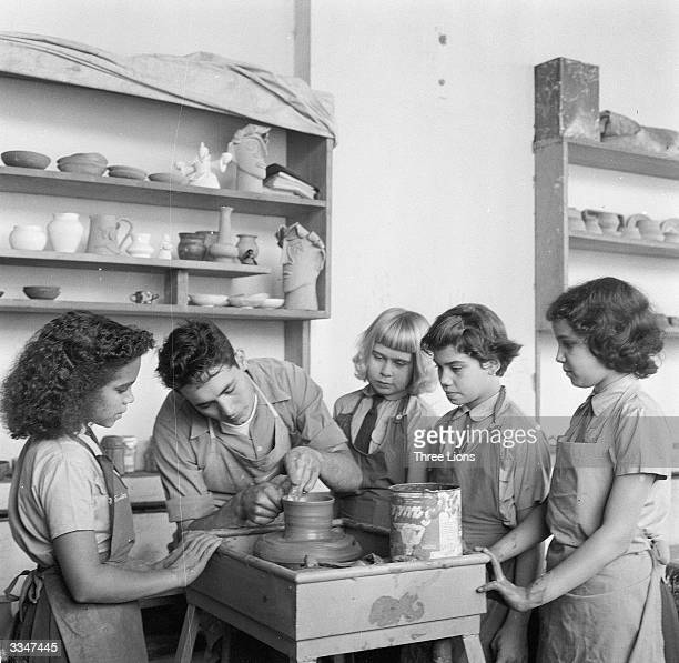 Pupils watching an instructor as he models a flower pot in the ceramics shop at the Central Educational Institute in Iraq