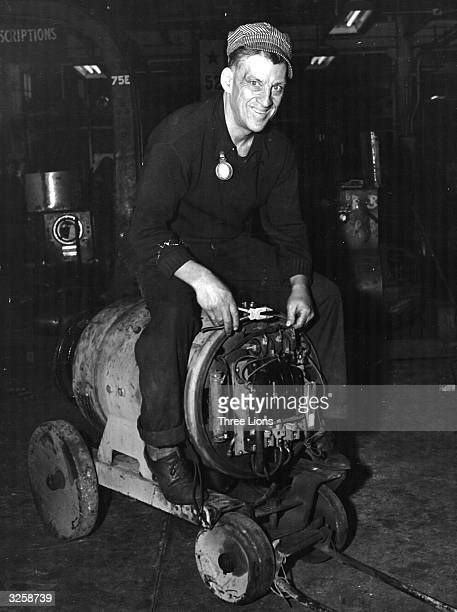 Reggie McNamara eight times winner of sixday cycle races sits astride a welding machine in a cycling position at US Steel's Federal shipyard where he...