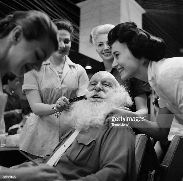Santa Claus gets a comb and manicure from a group of ladies at the start of the Christmas season in New York