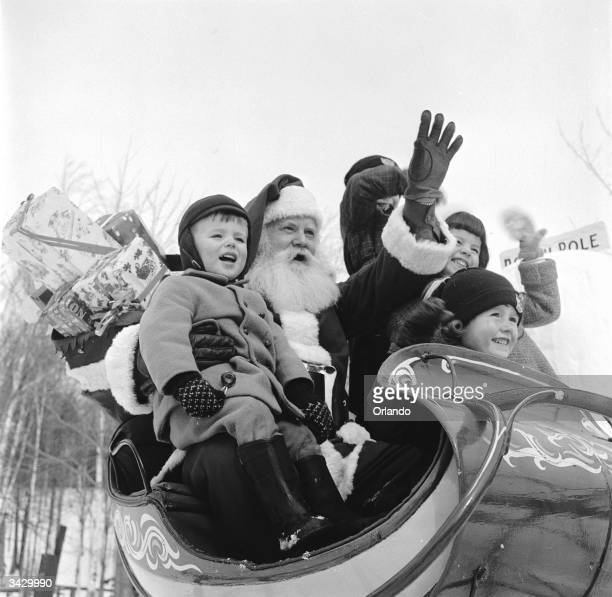 Santa Claus treats young visitors to a sleigh ride at his North Pole Workshop in the Adirondack Mountains of New York State