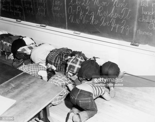 School children kneel to practice the 'Duck and Cover' airraid drill in an elementary school classroom