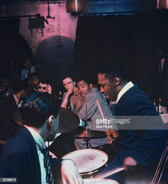 Side view of American jazz drummer and bandleader Art Blakey playing the drums as audience members watch from a table during a nightclub performance