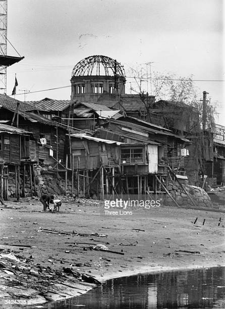 Slum dwellings at the foot of the 'A Bomb dome' along Motoyasu River, where families, suffering from radiation-induced diseases and injuries, live.