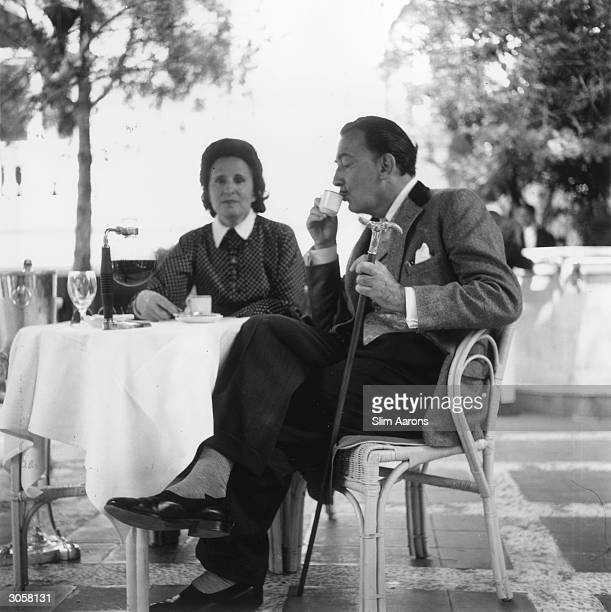 Spanish artist Salvador Dali enjoying a cup of coffee with his wife Gala on a terrace at the Ritz Hotel, Madrid.