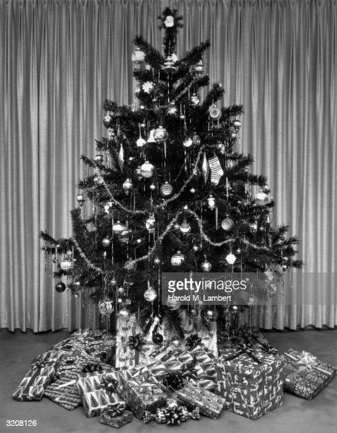Stilllife of a Christmas tree decorated with bulbs garland tinsel a stocking a Santa Claus and presents wrapped with holiday paper beneath