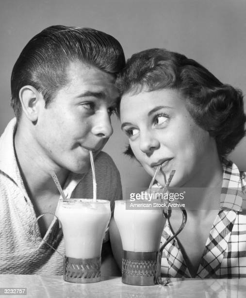 Studio headshot of a young couple gazing at each other with their foreheads touching as they each sip ice cream sodas through a straw