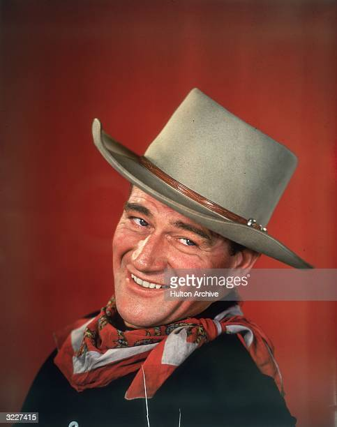 Studio headshot portrait of American actor John Wayne smiling in front of a red background dressed in Western garb with his head turned to the side