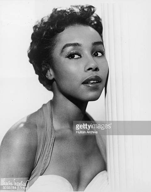 Studio headshot portrait of American singer and actor Diahann Carroll wearing a sleeveless dress leaning against a white column