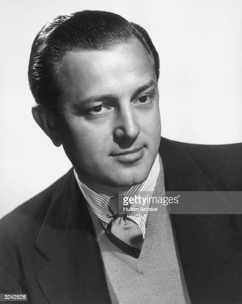 Studio headshot portrait of Canadian-born film director Edward Dmytryk . Dmytryk is wearing a striped shirt with a tie under a V-neck sweater and a...