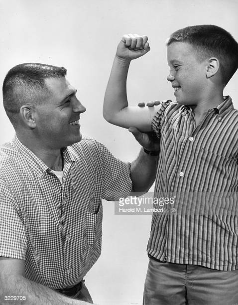 Studio image of a young frecklefaced boy flexing his arm in order for his father to feel his bicep 1950s