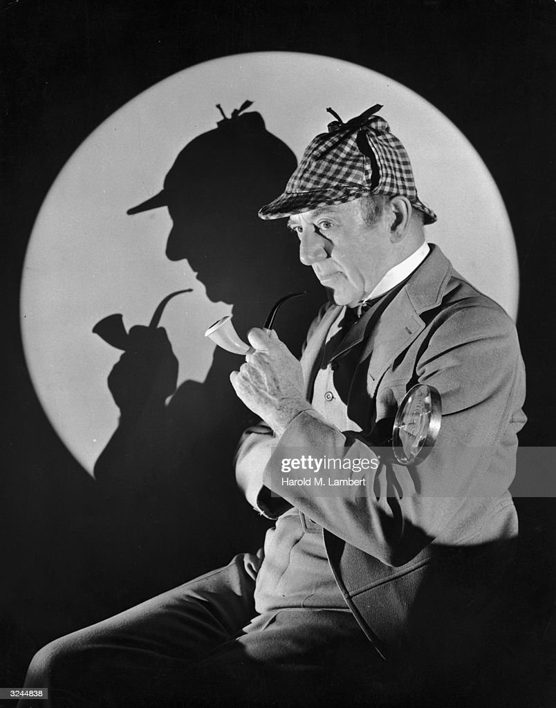Studio portrait of a man dressed as British detective Sherlock Holmes with a plaid cap, a meerschaum pipe, and a magnifying glass. His silhouette is visible in the background.