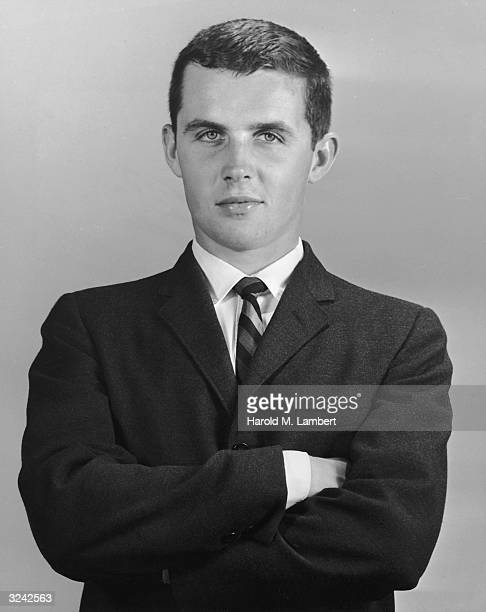 Studio portrait of a young man wearing a coat and tie with his arms crossed 1950s