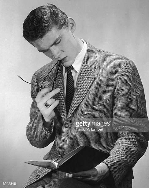 Studio portrait of a young man wearing a tie and sportscoat while holding his eyeglasses to his lips and reading a book 1950s