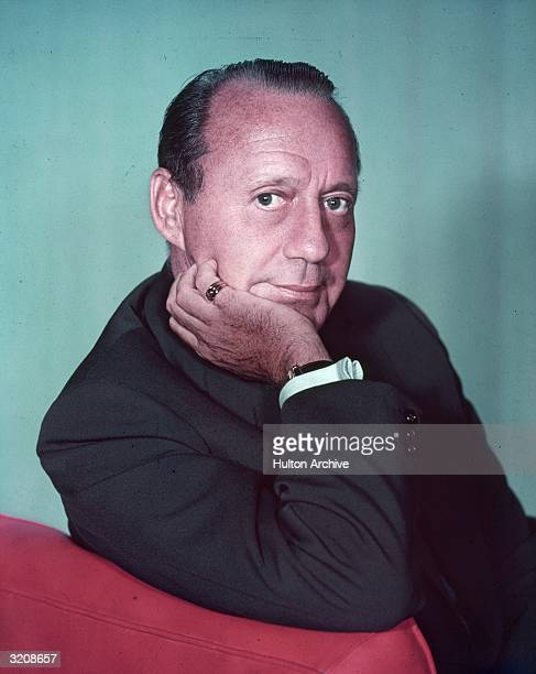 Studio portrait of American actor and comedian Jack Benny resting his chin in one hand as he looks over the back of a red chair in front of a green...