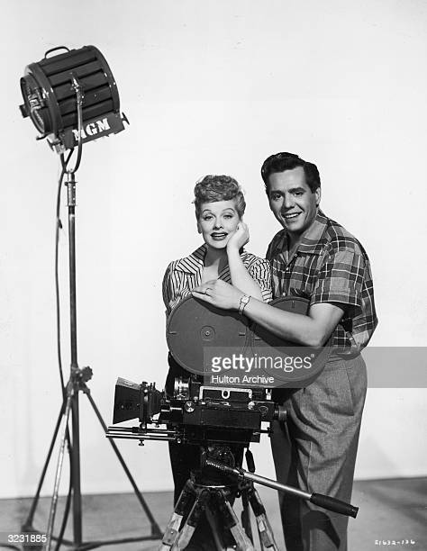 Studio portrait of American actor and comedian Lucille Ball and her husband, Cuban-born actor and bandleader Desi Arnaz , posing behind a motion...
