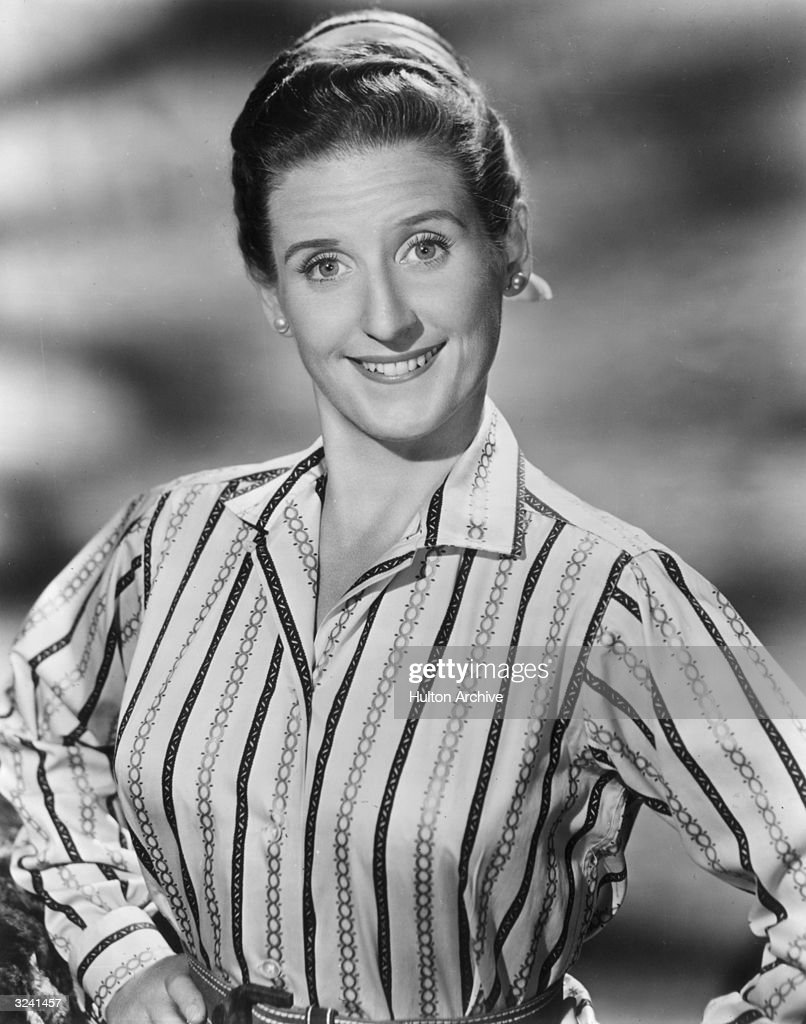 Studio portrait of American actor Ann B Davis smiling and putting her hands on her hips. She is wearing a scarf in her hair and a striped blouse.